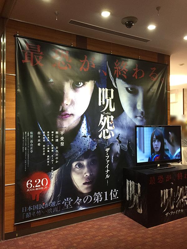 新宿バルト9、ホールに掲示された大型テナントと、モニターで上映中の予告篇映像。