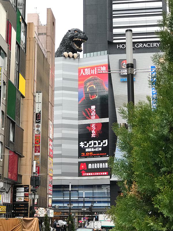 TOHOシネマズ新宿外壁に飾られた大看板と、それを見おろすゴジラ。