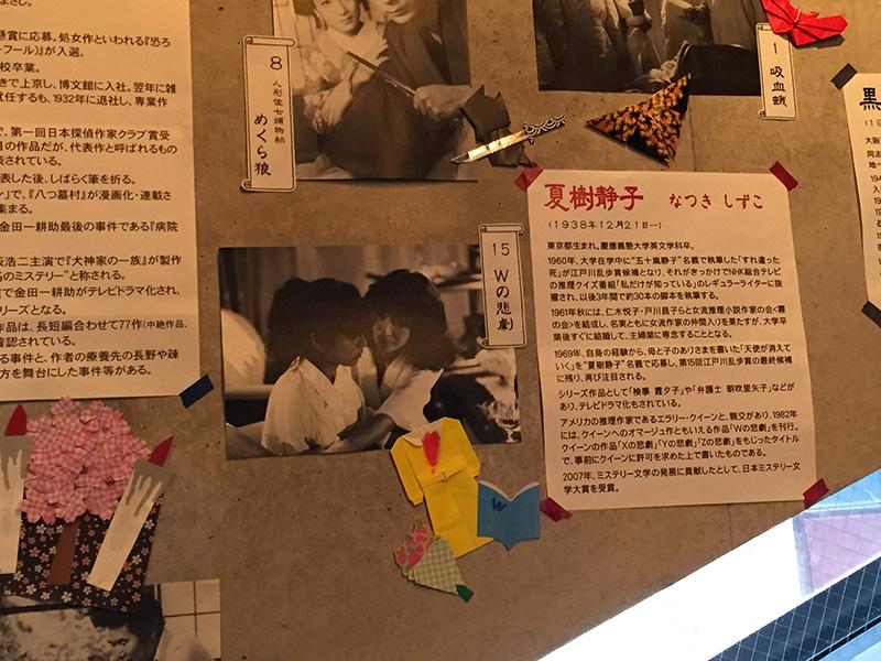 神保町シアターのロビー壁面に掲示された劇中のスチールと、原作者の経歴紹介文。