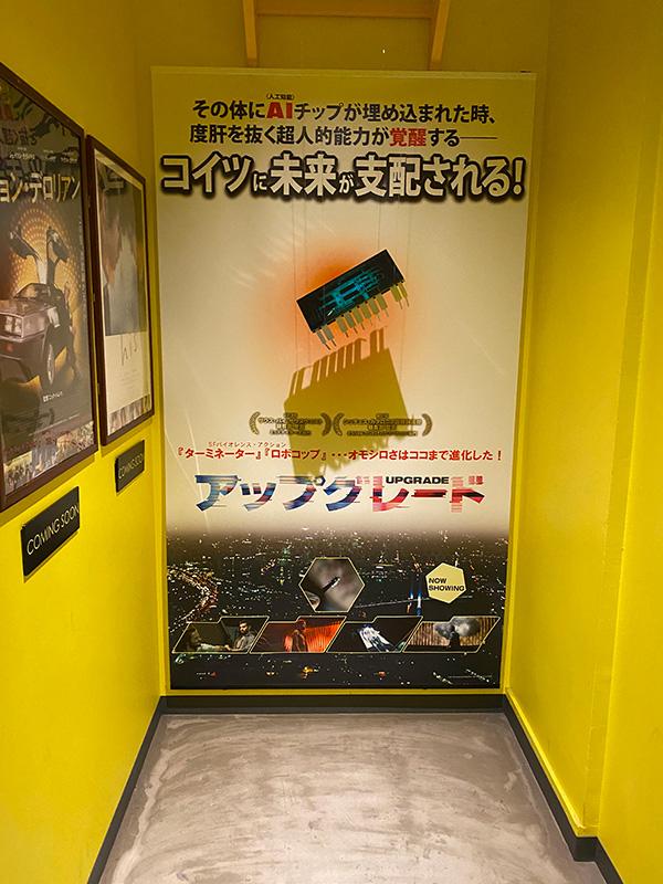"""新宿シネマカリテ、階段脇の空間に展示されたイメージと""""STEM""""のモニュメント。"""